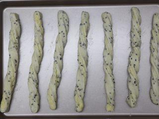黑芝麻椰蓉面包棒,取一份小面团,两手向相反的方向搓成螺纹条,放在垫好油纸的烤盘上稍微按压下,不然最后发酵后和烤时卷会散开了就不好看了