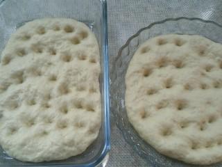 佛卡恰面包,取出发酵好的面团,用手深深按几个洞