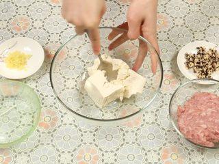 豆腐丸子汤,将豆腐放入一个大碗里,用勺子背面压成豆腐泥,肉末跟豆腐的比例为1:1。