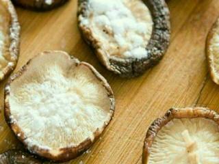 肉酿香菇,3.香菇用砧板压平,将一半内里朝上撒上淀粉。