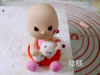 翻糖蛋糕--树桩上的小女孩儿,中间丢了几张图。搓一个小水滴型做兔子的身体,用做小孩儿头的方法坐兔子的头,再粘上耳朵,贴在小孩儿身前,再做出手臂抱的动作,然后搓4个小球做兔子的四肢