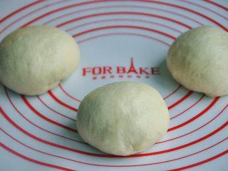 黄油椰蓉吐司条,将面团取出,按揉排气后面团均分成三团,盖上保鲜膜松弛15分钟。