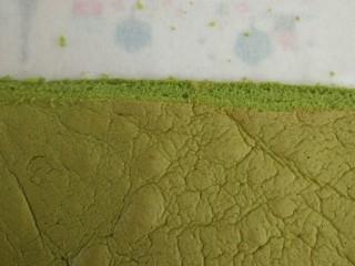 日式抹茶红豆草莓瑞士蛋糕卷(超详细),蛋糕卷出炉脱模后放凉大约10分钟就可以开始卷了,千万不要等凉透了卷,那样会裂开的。 先在蛋糕块的底部铺上1张长约40厘米的油纸,只有油纸够长,才好卷蛋糕和定型。  因为是反卷,所以蛋糕块的毛巾面贴着油纸,在底部,切除蛋糕2端硬边边,其中离身体远的那边切成斜边形状,方便卷卷固定和定型。