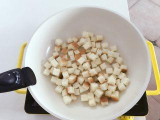 宝宝辅食:吐司爆米花-24M+ ,把吐司切小丁,放入平底锅中小火烘成边缘金黄,取出备用,烘的时候可以用勺子搅拌下,让吐司上下都受热。 》要控制好火候哈,不要烘焦。