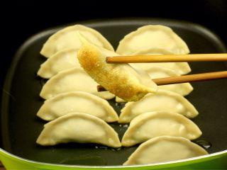 猪肉卷心菜煎饺,平底不粘锅加油,并排放入煎饺煎至底面金黄色,