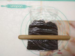 免烤快手高颜值的甜点——火龙果慕斯蛋糕 ,奥利奥饼干碎放入保鲜袋中,用擀面杖擀成粉状。