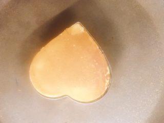 舒芙蕾厚松饼(无泡打粉版),翻面继续煎1~2分钟,同样盖锅盖。煎的时候时刻注意不要糊锅。用牙签插入看有无残渣来判断生熟。脱模的时候注意不要烫着。