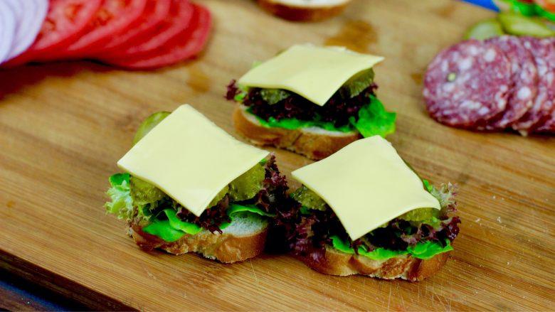 开放三明治,芝士片摆放在酸黄瓜片上