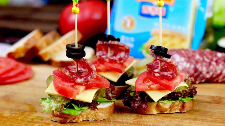 开放三明治,用竹签串上<a style='color:red;display:inline-block;' href='/shicai/ 2393'>黑橄榄</a>洋葱圈和萨拉米肠串在摆好的三明治上