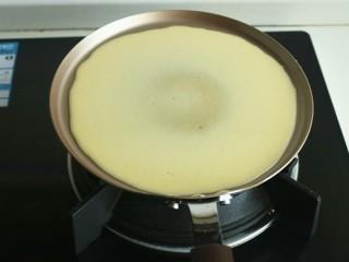 木瓜班戟,轻轻转动锅子,让面糊均匀铺满整个锅底。
