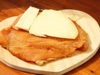 芝士爆浆鸡排,6、将切好的芝士片放到鸡胸肉里,盖上。