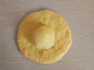椰蓉花朵面包,松弛好的小面团压扁,包入椰蓉馅。