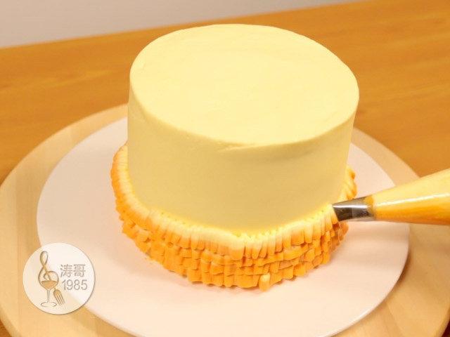 黄桃裙边蛋糕,一边挤一边慢慢转动蛋糕转盘,转盘转动的速度要比挤出来的速度慢,这样就能挤出褶皱的裙边效果,一层一层往上挤