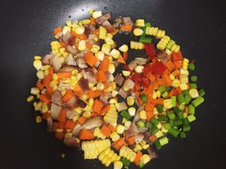 夏威夷菠萝炒饭,下油锅先翻炒玉米粒,胡萝卜粒,叉烧粒,蒜苔粒。炒好后装碗放置一边