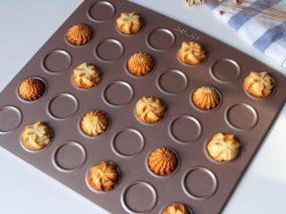 花样黄油曲奇,把烤盘放入预热好的烤箱中层,因为两种造型的曲奇厚度不一,所以烘烤是时间也不同,2D花嘴挤出来的曲奇烘烤时间是12分钟左右,4B花嘴挤出来的曲