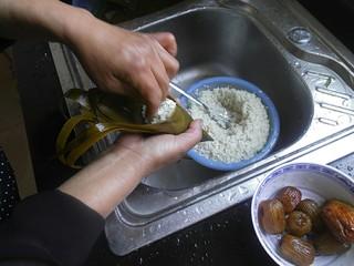 传统红枣粽,放入红枣后,在用勺子挖少许糯米,将红枣盖住即可。接着在用手把糯米给推紧实一点