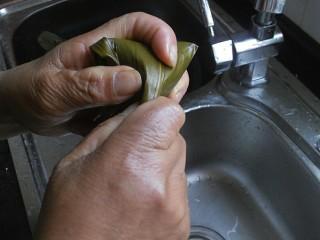 传统红枣粽,然后将上方的粽叶折过来,同样也要拉紧一点,然后将剩余的粽叶小尾巴顺着粽子裹一下就可以了