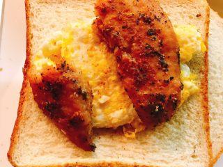 煎鱼吐司,将煎好的鱼放在煎蛋上