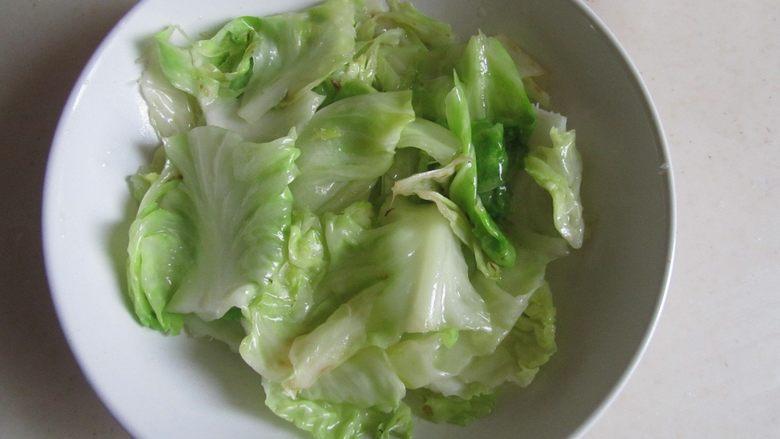 金汤龙利鱼,将炒过的包菜叶片垫入碗中;