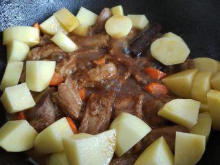 土豆烧排骨,将洗净去皮的土豆和胡萝卜放入,小火焖一会儿