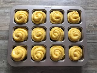 胡萝卜椰蓉卷,取出二发的面团,烤箱170度预热。 二发好的面团表面刷一层蛋液。