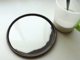 凉皮,找一个不沾的平盘,我用了披萨盘,舀入适量面糊,转动盘子使面糊铺满盘子。