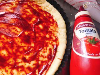 西班牙香肠披萨(快手版),披萨皮烤好了,涂抹上一层番茄酱。