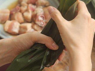 粤式海鲜咸肉粽,再拿一张粽叶铺在上面,两边向中间折起,上面再对折到中间;