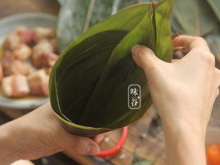 粤式海鲜咸肉粽,取2片粽叶错开一点相叠,折成一个漏斗形;