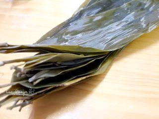 蜜枣白米甜粽,准备粽叶。 干粽叶用水煮开,浸泡过夜。 这样处理过的粽叶不易破裂有韧性, 而且吃的时候打开不会粘住米。