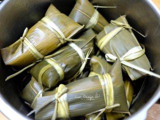 蜜枣白米甜粽,边包边放进锅里。 全部包完之后,倒水没过粽子。 肉粽子一般用久煮更入味更好吃, 这样肥肉都煮得晶盈剔透煮化了, 这个甜粽子因为只有蜜枣, 所以我就偷懒了。 两种方法,随便泥萌选择。 方法1:大火烧开转小火,煮2个小时, 然后浸泡过夜,这样最入味。 方法2:懒惰的办法, 高压锅20分钟,然后浸泡过夜。