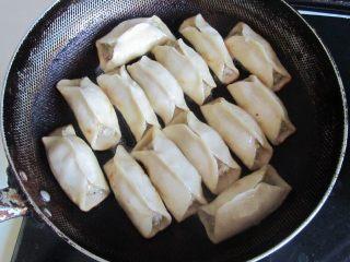 西葫芦肉馅锅贴,水快干时,转为小火, 慢慢的将锅贴煎至金黄色;