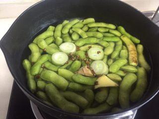 糟卤毛豆,锅里放水、葱、姜、花椒把毛豆煮熟,水开煮五分钟左右就熟了。
