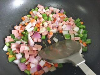 粗粮凤梨炒饭,加入洋葱丁、青椒丁、火腿肉丁继续翻炒。