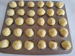 红豆沙小餐包,发酵好的面团取出来,刷上鸡蛋液,撒上白芝麻
