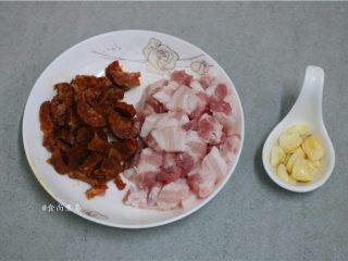 五花肉蒜香腊味焖饭,接着处理配料:腊肠焯熟切粒,五花肉洗净切粒、蒜瓣去皮拍碎