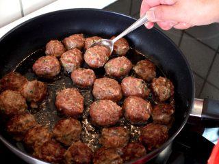 茄汁牛肉丸子烩饭, 6.平底锅倒入略多些油,油要完全盖住锅底。 当油温热的时候,用虎口挤出一个丸子,然后用个小勺子挖入油锅中,就这样做完全部的丸子。