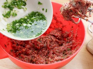 茄汁牛肉丸子烩饭, 4.将15克姜和50克葱切碎加水(约90ml)分多次拌入肉泥馅中,搅拌上劲。注:可以借助电动打蛋器。