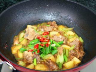 香辣土豆猪骨干锅,煮至汤汁收干,土豆绵软、加上蒜叶和小米椒,翻炒均匀即可