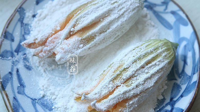 酥炸南瓜花,另外取一个碟子放入适量面粉,把南瓜花放在面粉上滚一圈;