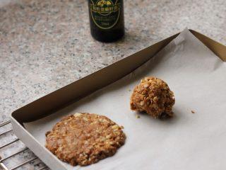 燕麦核桃饼干,7、烤盘上铺上烘焙纸,取出大小适中的一块燕麦泥,放到烤盘上,压成厚薄约3-5毫米厚薄的饼状。