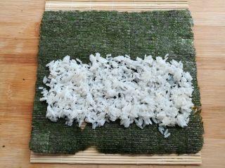 金顶寿司,在寿司帘上放上大片的紫菜,铺上一部分的米饭,前段留一半,末端留一小节不铺米饭