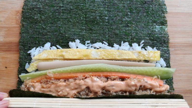 金顶寿司,提起寿司帘的末端,紫菜包住饭团的材料