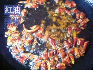 红油辣椒,花生碎稍微变色,立即投入备好的干辣片,锅里随即起沫。