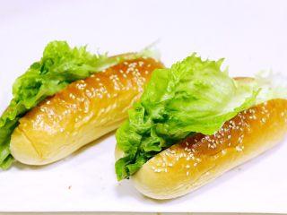 热狗面包,待面包放凉后,用锯齿刀在面包中间切一刀,不要切断,铺上生菜叶。
