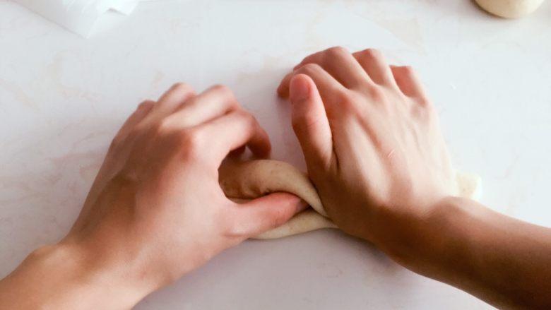 高纤低脂的全麦蔓越莓贝果,左手对折,右手掌根处压紧。