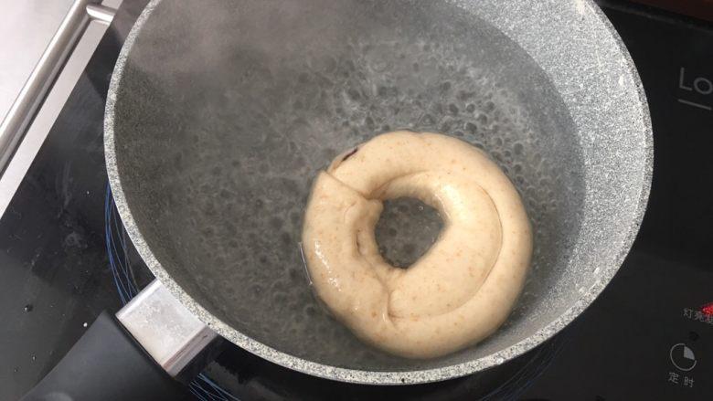 高纤低脂的全麦蔓越莓贝果,4)煮糖水  糖水沸腾后转小火煮贝果。正反各30秒。  发酵完成的贝果,是可以浮在水面上的,如果下沉,捞出后擦干水分继续发酵。