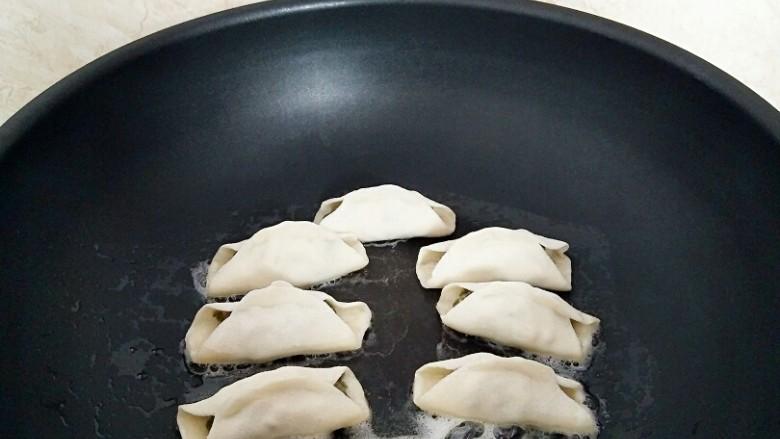 早餐锅贴,煎锅中放入2汤匙玉米油,摆放锅贴,中小火烙至底部金黄色色。