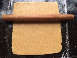 黑米年轮小卷饼干,操作台上贴一张保鲜膜,把面团放上用擀面杖擀开成长方形状。