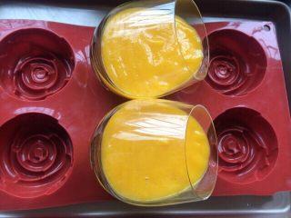 芒果酸奶冻,把杯子斜放在模具里或其它的物体托中,倒入芒果泥,放入冰箱冷藏2-3小时定型。